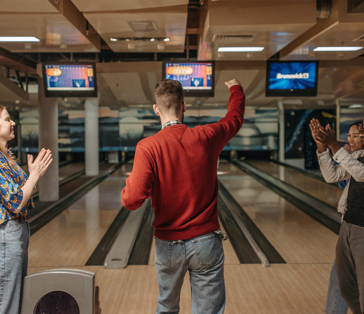 Young Adult bowling with friends celebrating