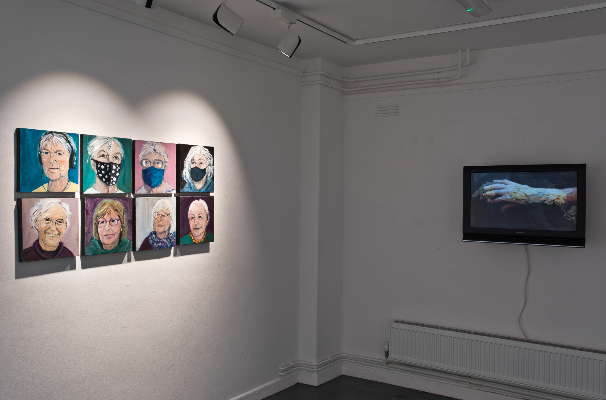 Installation view - Na Cailleacha - portraits by Patricia Hurl / On the Monitor - Barbara Freeman, Seven Voices, Video Artwork - 25 mins - Na Cailleacha, Stone Sounding, 2020, collective video performance, directed by Carole Nelson & Therry Rudin