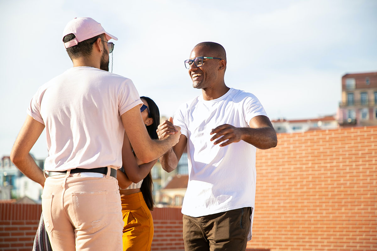 Group of friends greeting each other on a rooftop