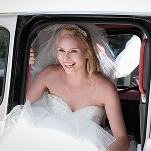bride getting out of wedding taxi