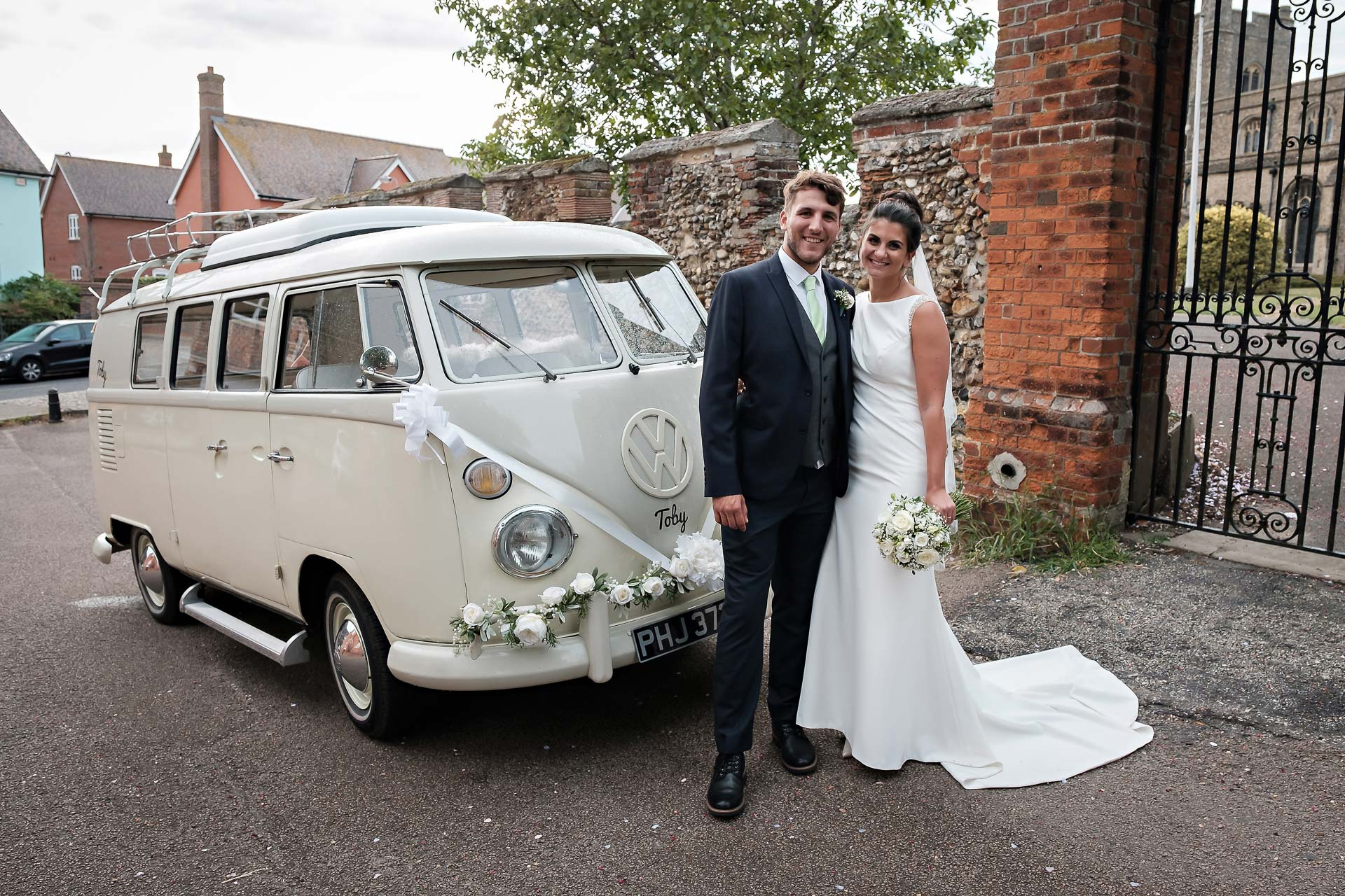 bride and groom standing in front of a VW camper van used as a wedding car