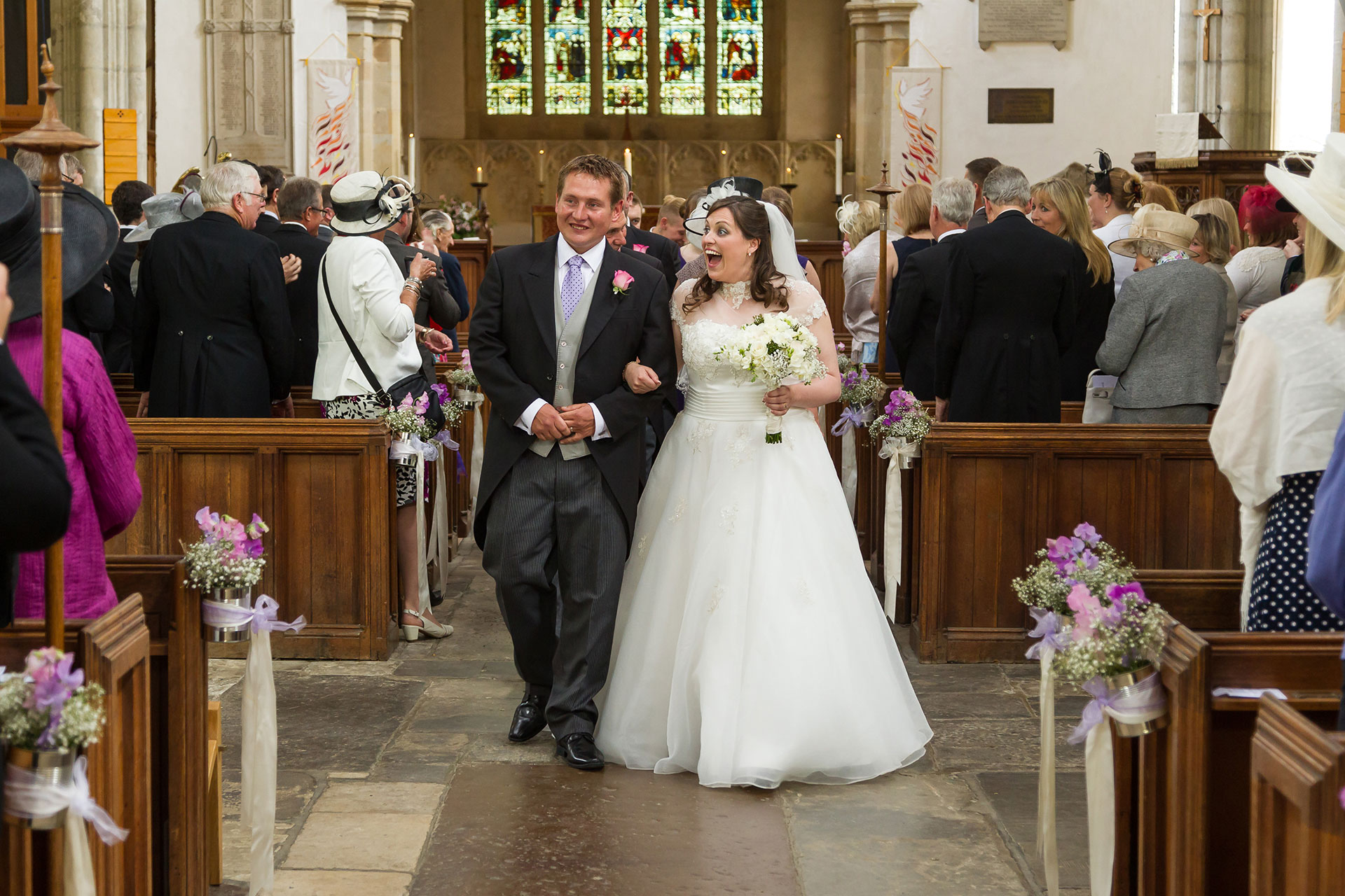 bride and groom coming down the isle in a church