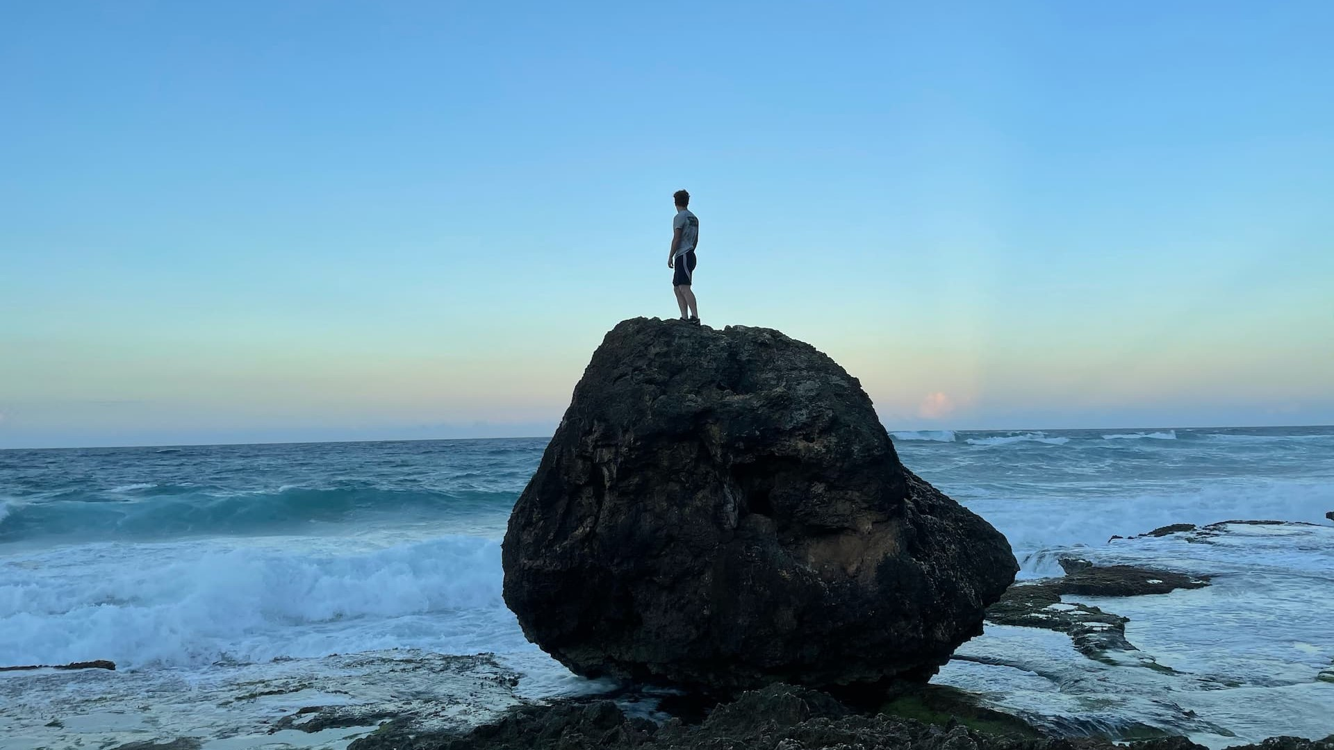 A person standing on top of a rock.