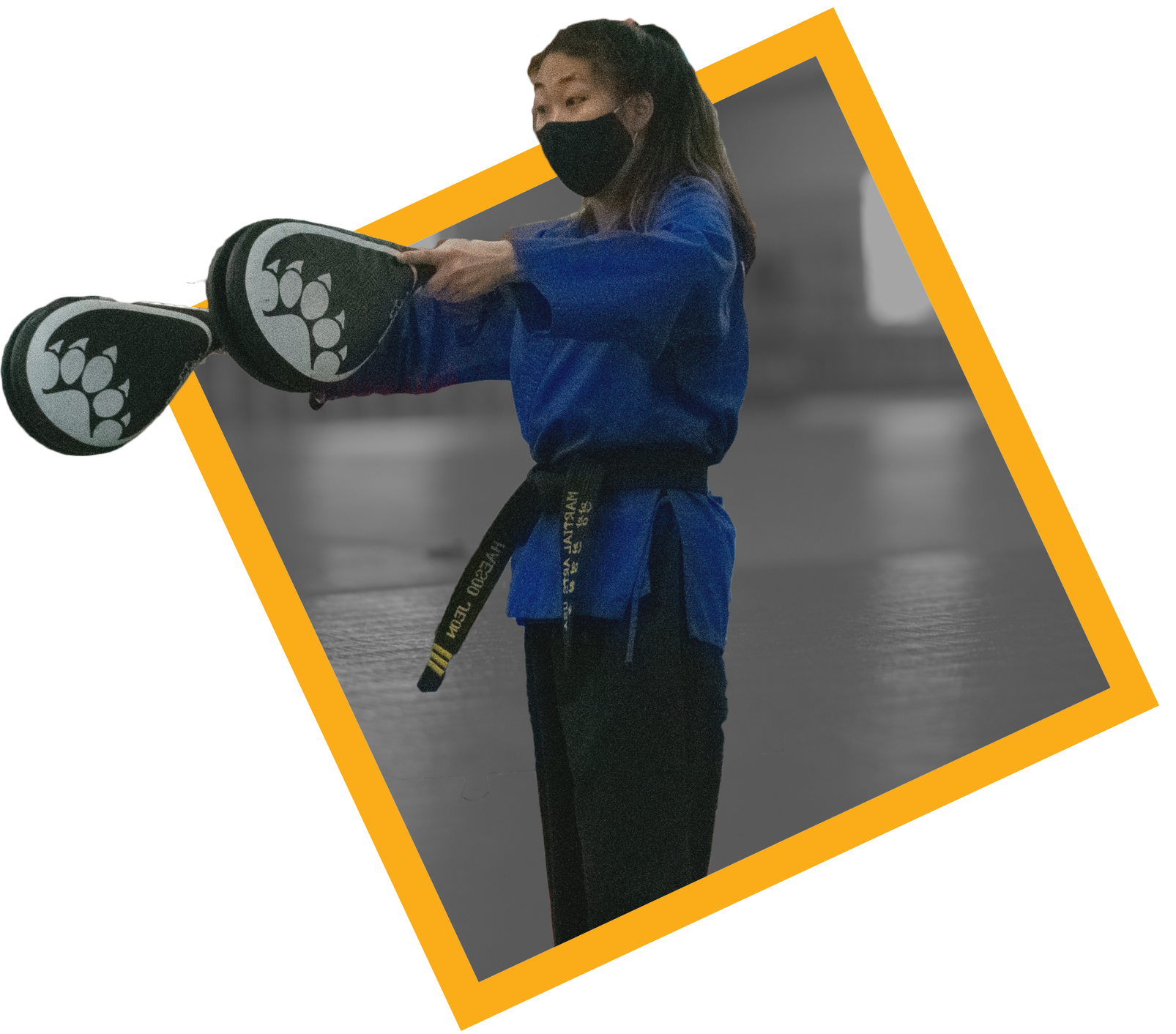 Instructor holding pads for students to practice taekwondo.