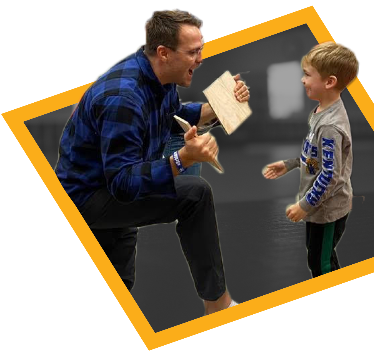 Father and Son celebrate as son breaks a board with a Karate Punch.