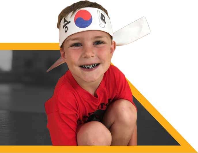 Happy child smiling wearing a Martial Arts headband.