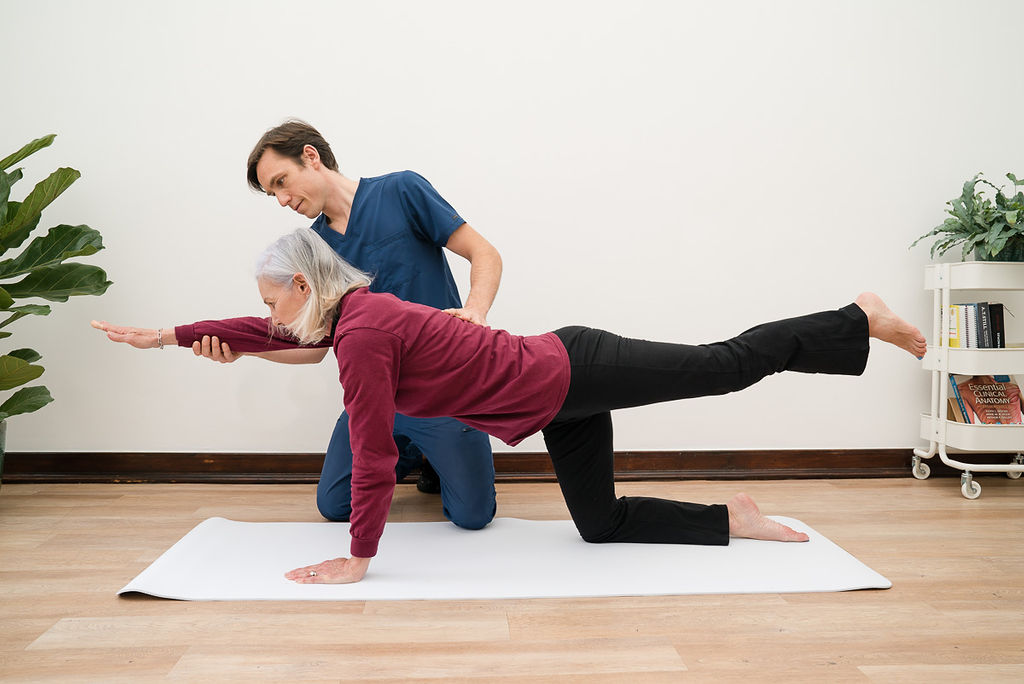 Osteopath correcting client when performing exercise.