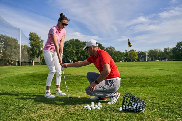Golf Pro correcting women who is learning to play golf.