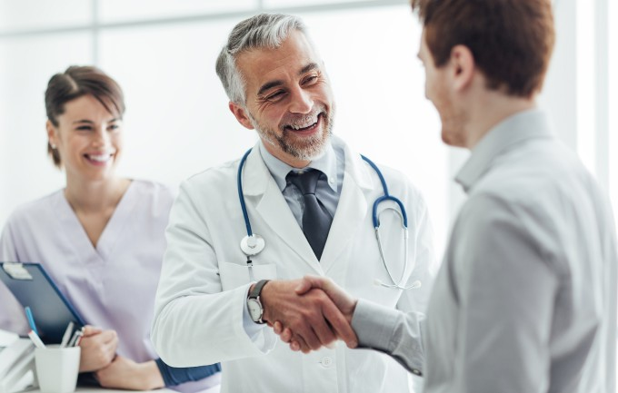 Doctor in clinic giving handshake to his patient