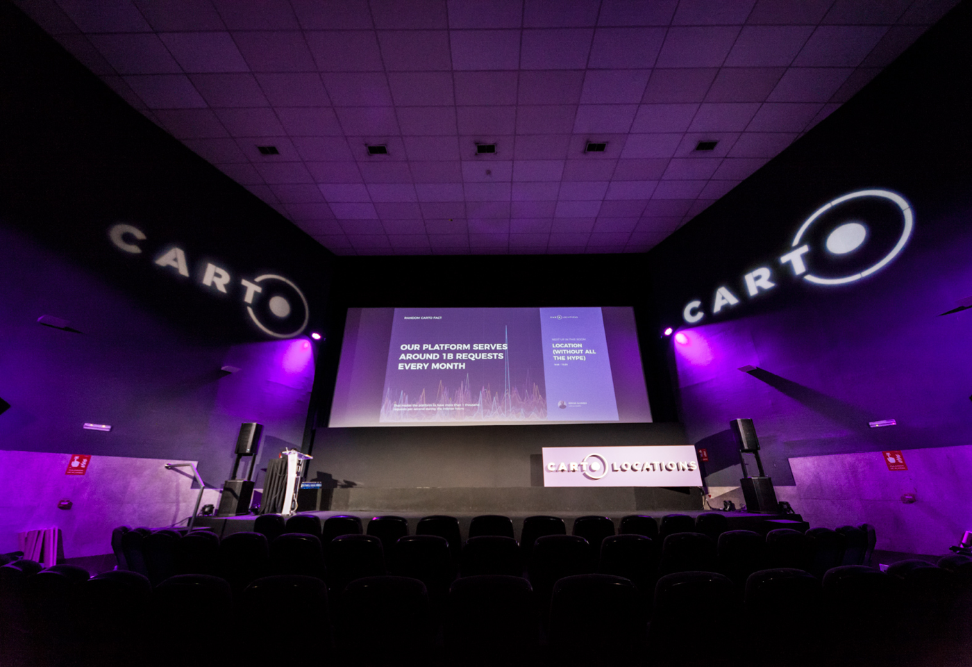 Carto Locations venue, with the logo projected over the walls and purple lights lighting the space