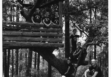 Old photo of people in a tree house