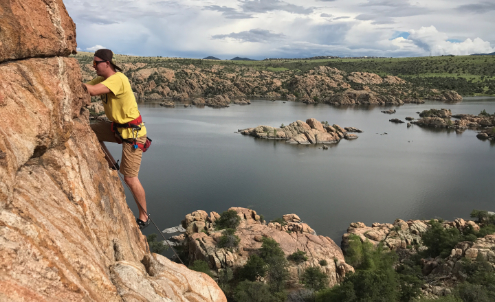 man rock climbing with view of lake in the background