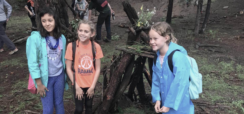 Kids standing around a campfire