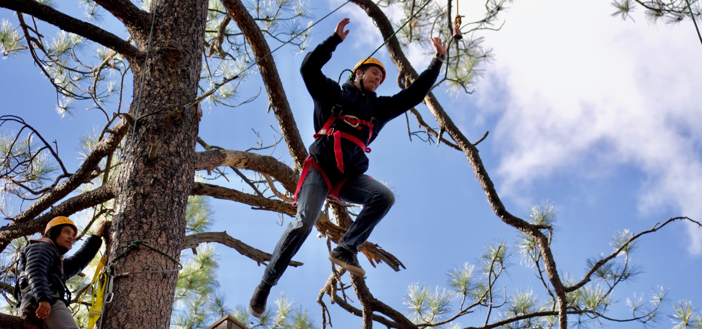 Man jumping in the Leap of Faith Ropes course