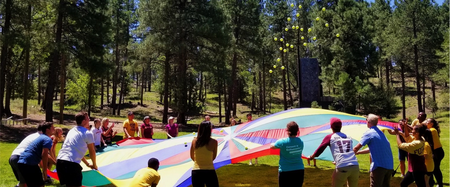 People playing with tennis balls on a parachute