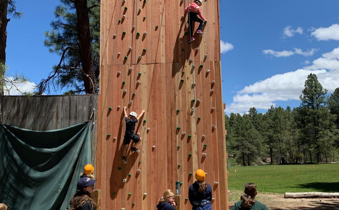people climbing on a climbing wall