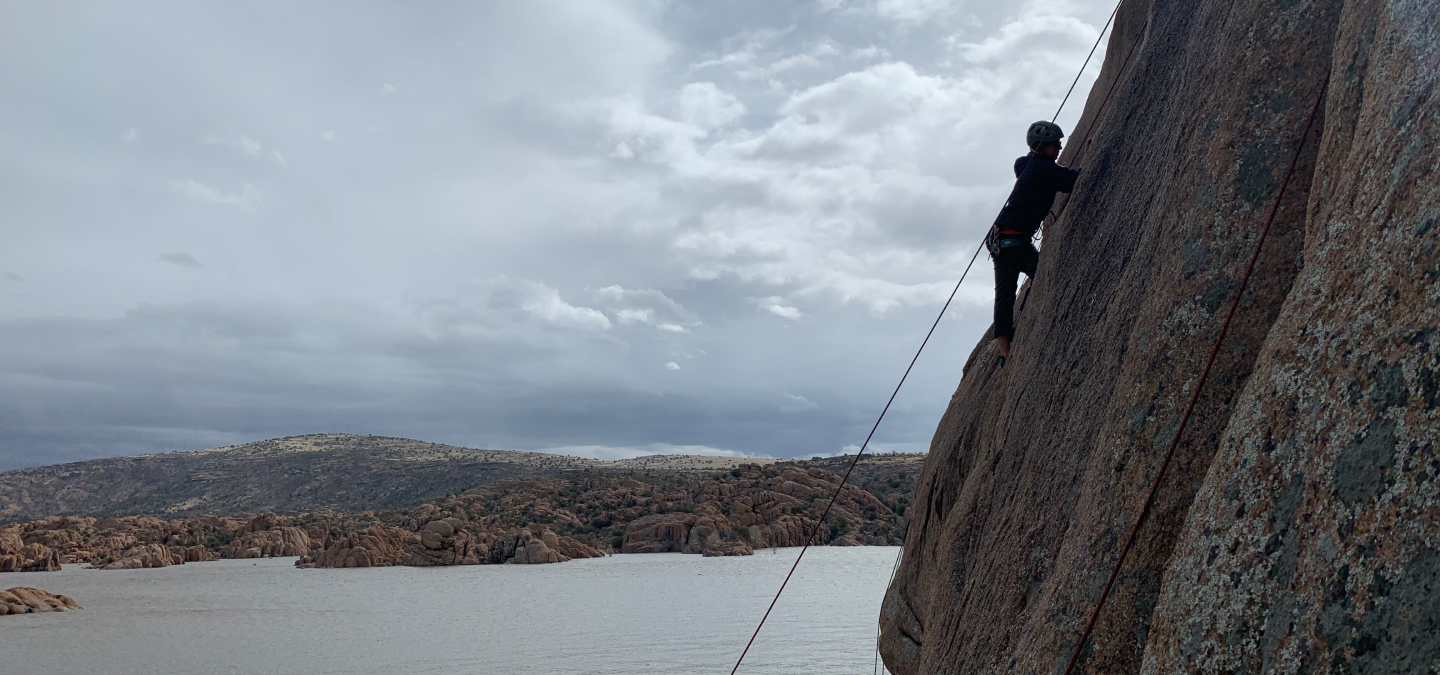 Person rock climbing with view of lake in the background