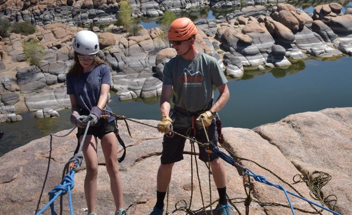 People wearing rock climbing gear on top of a rock