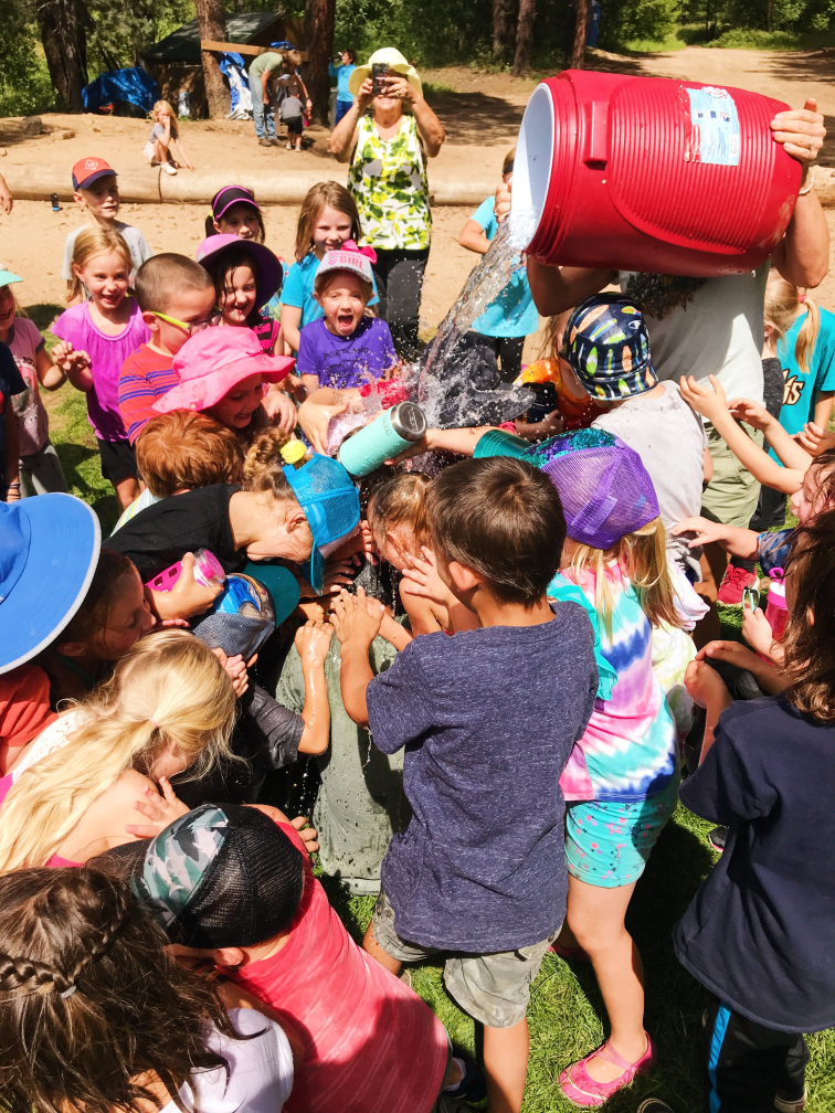 campers dumping orange cooler over teacher after a successful day on the challenge course