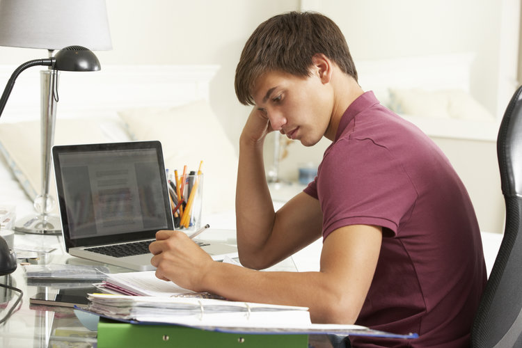 A young man holding a pen and looking at a screen