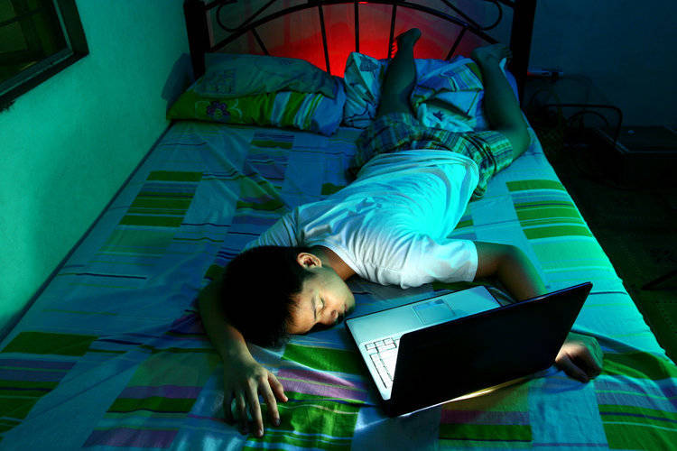 A male sleeping with a laptop