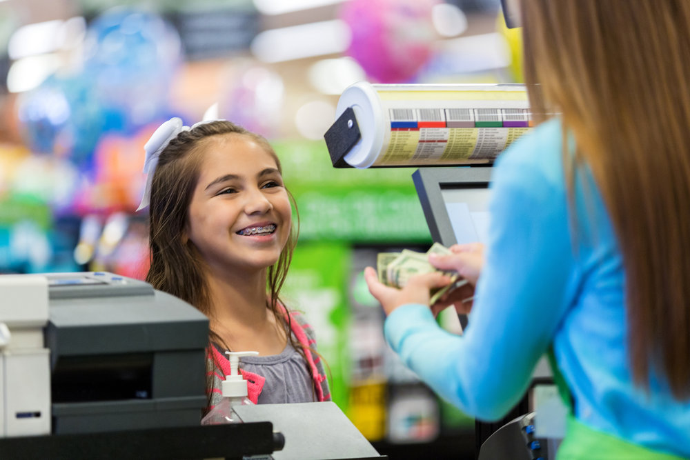 young girl paying at the cashier