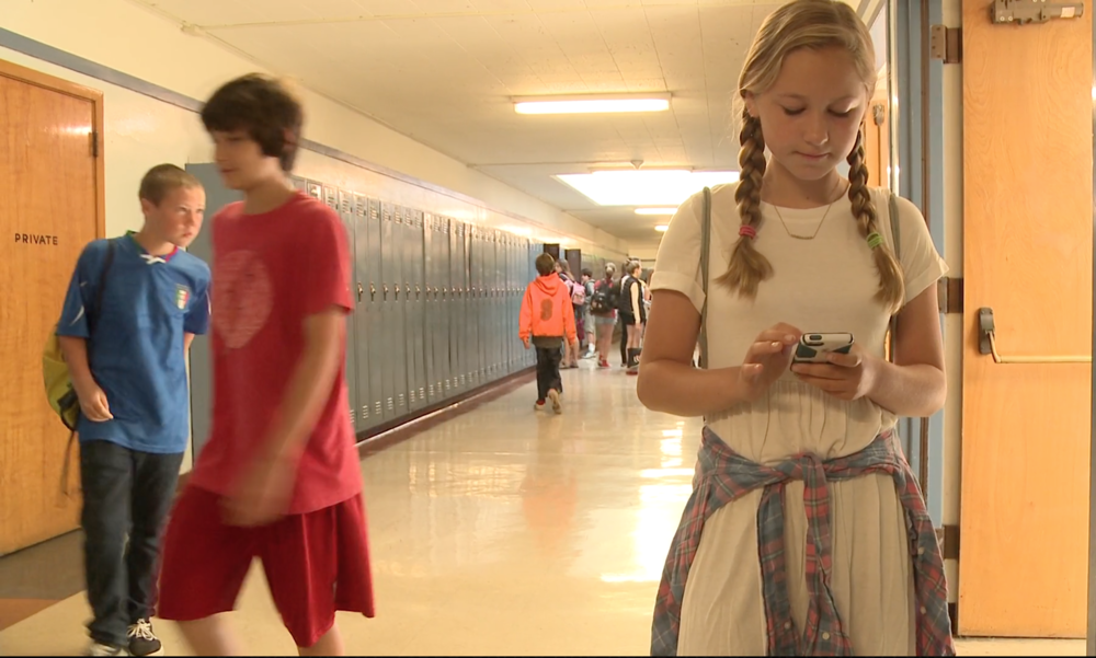 Girl using phone with 2 boys in background