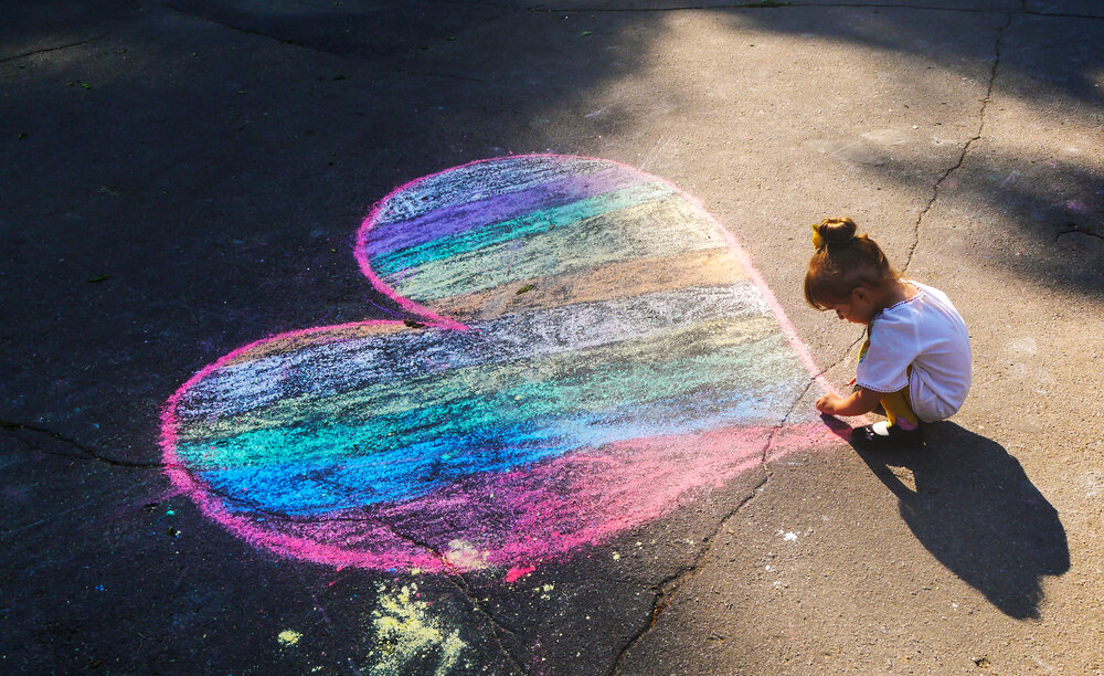 young child drawing a love heart on floor