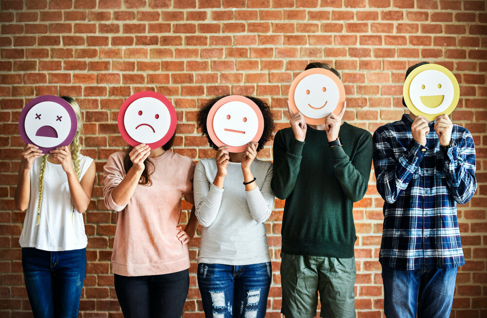 group of people holding faces over their face