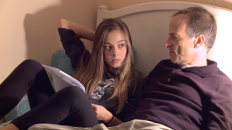 girl and father reviewing screen time contract