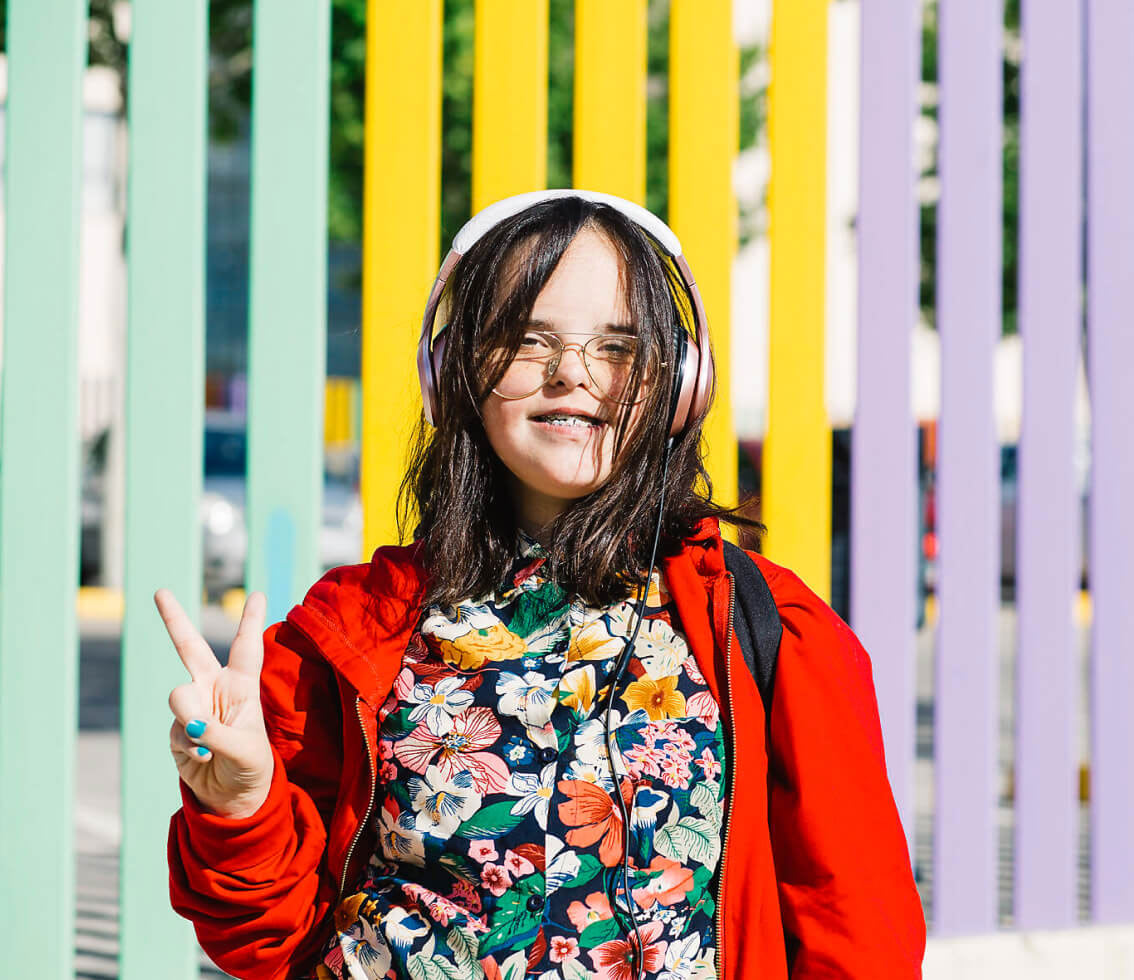 Teenager with down syndrome in brightly colored clothes and headphones giving peace sign in front of a painted fence.