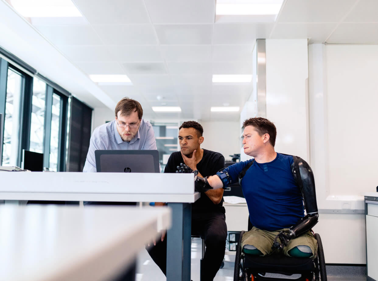 Man with prosthetic limbs in wheelchair points at computer with two other men.