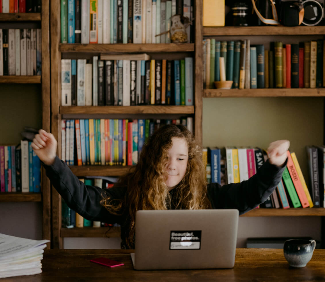 Teenage girl with curly hair at computer with arms raised in celebration