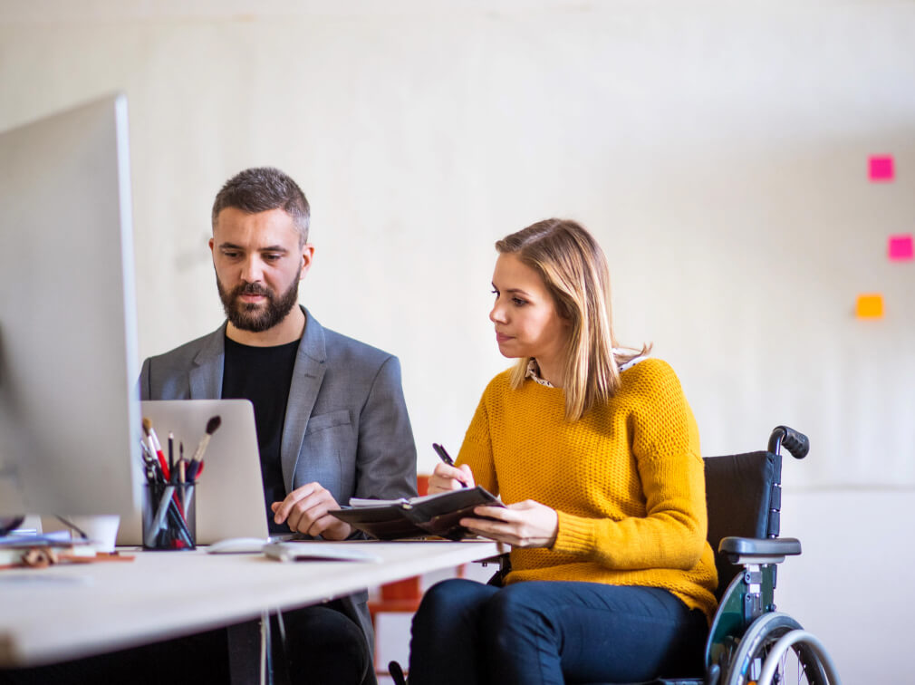 Woman in wheelchair in meeting with man at computer