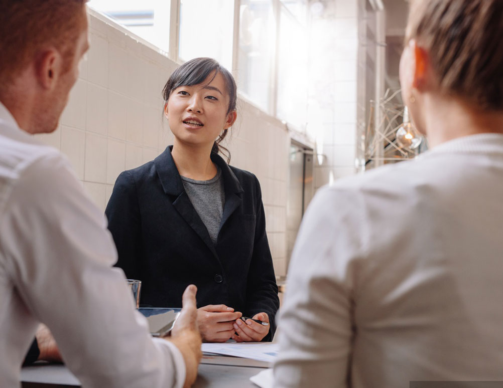 A white man and woman and an Asian woman in a meeting