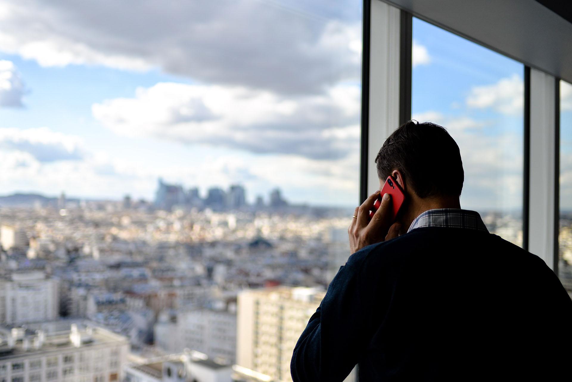 Muž stojící před oknem s červeným telefonem u ucha