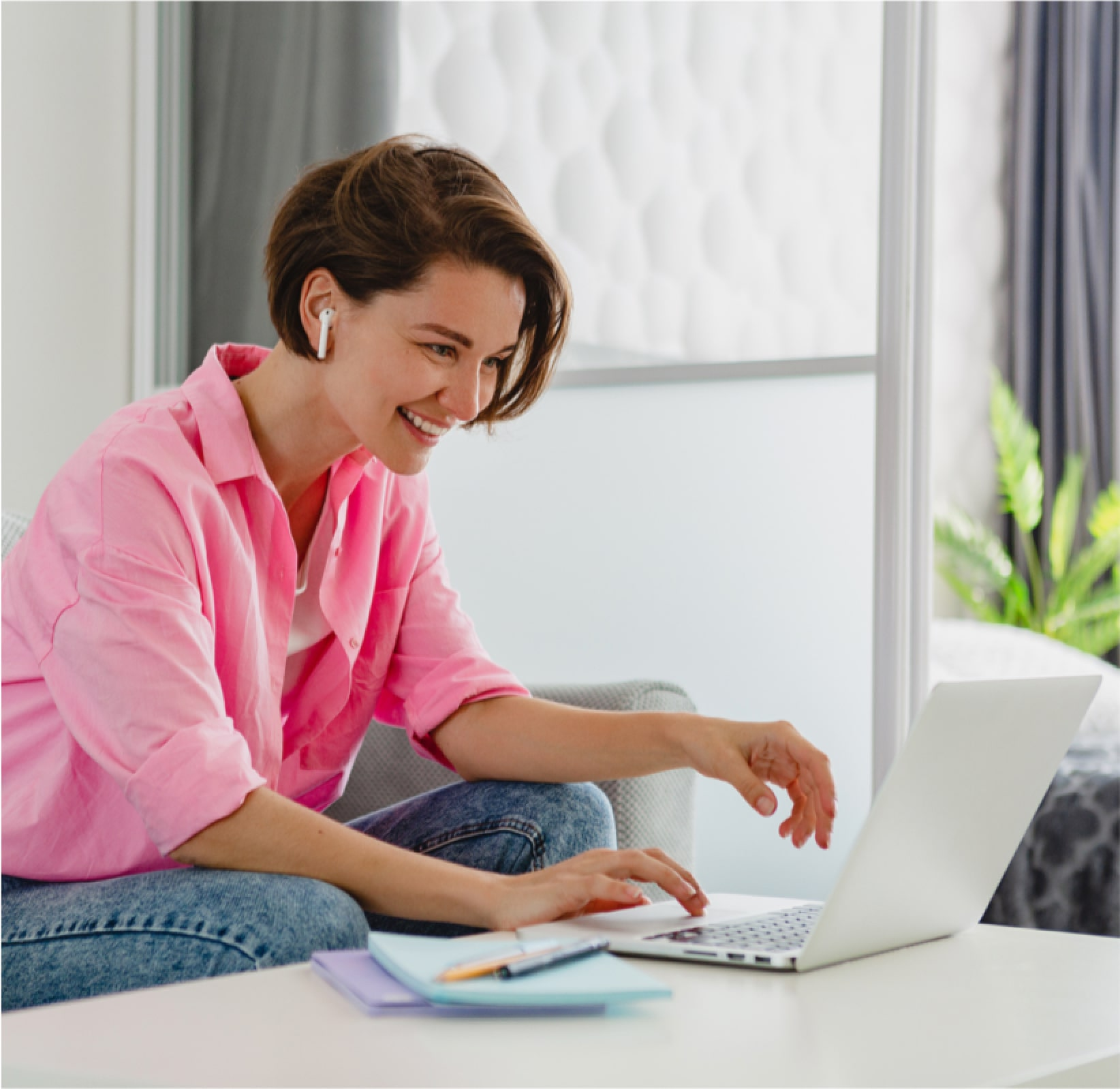 smiling woman in a pink shirt works on her laptop.