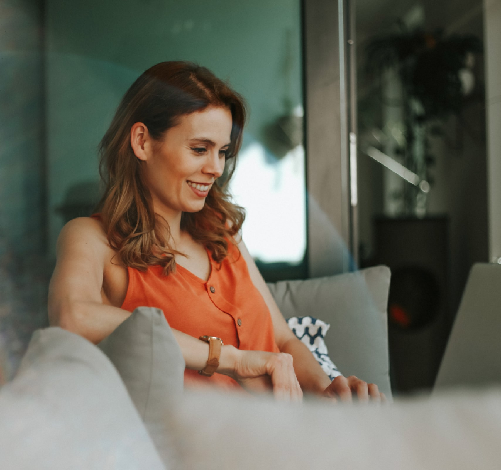 woman in orange blouse working with laptop while sitting on sofa