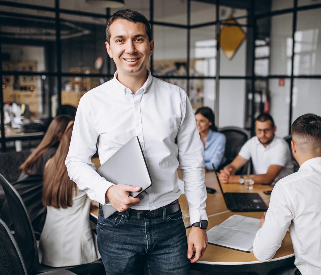 man holding laptop smiling at camera