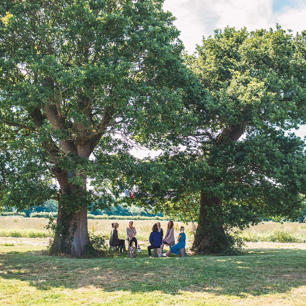 Group of women sat in a circle under trees