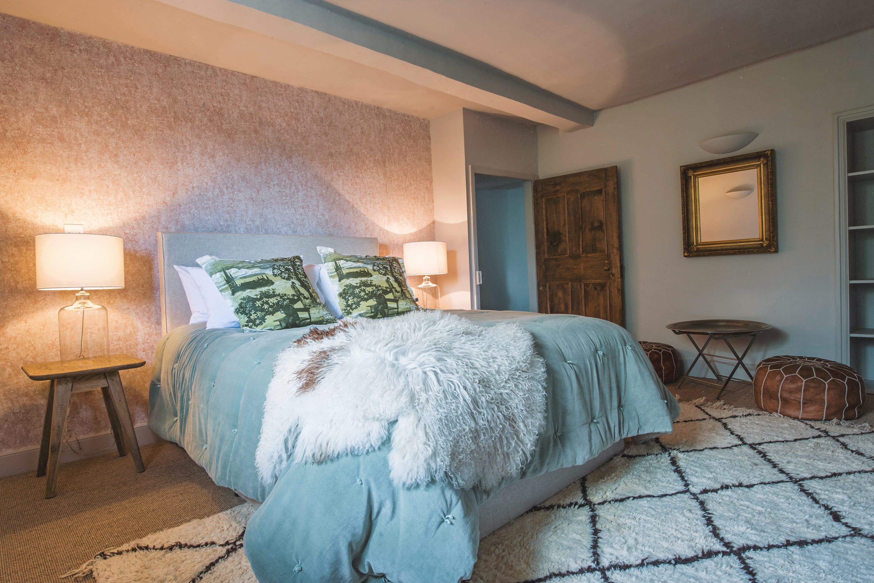 King bedroom with cozy bed and sheepskins