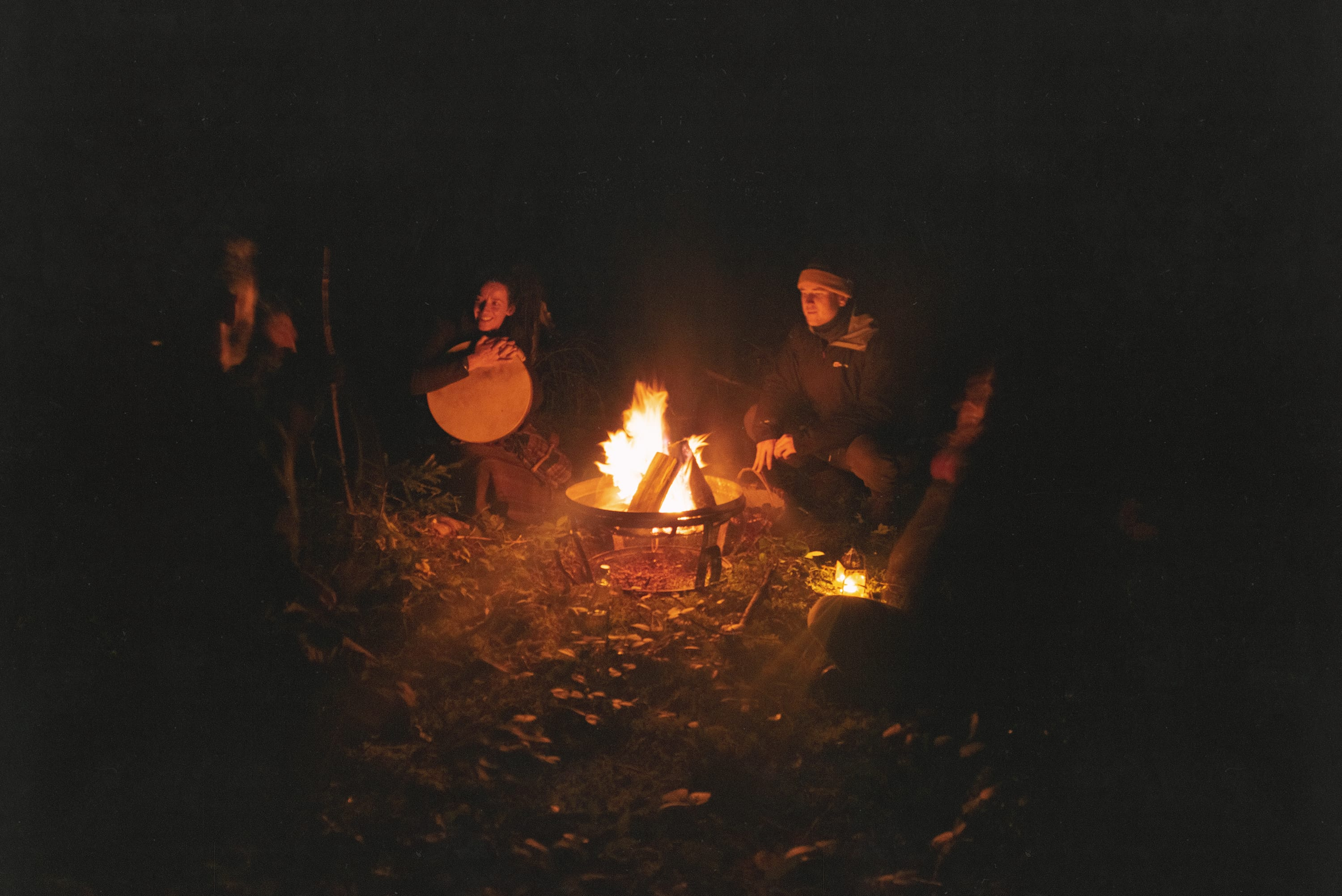 Group of people sat around a fire in the dark