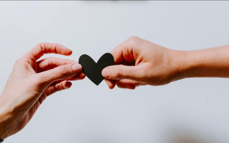 2 mains tenant un coeur entre leurs doigts