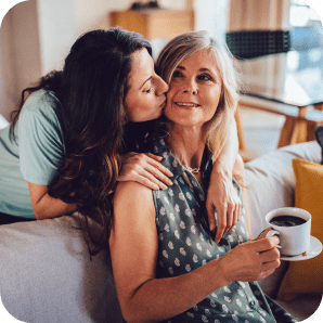 A daughter giving her mother a kiss on the cheek.
