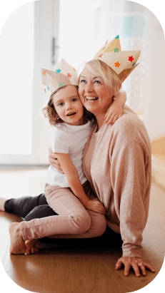A grandmother and granddaughter playing together on the floor.