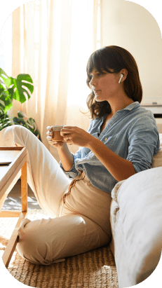 A young woman listening to music while sitting in her living room.