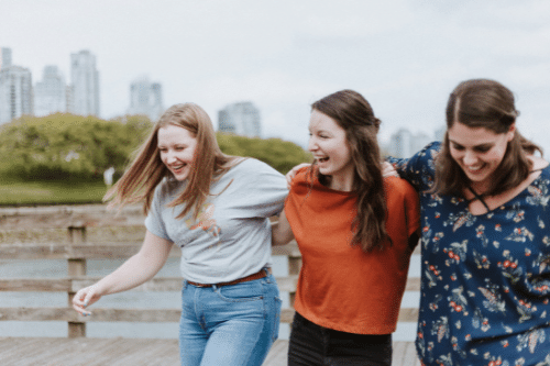 let down by friends; group of young women holding each other walking
