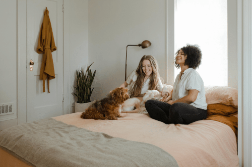 feeling let down by friends; two women sitting on bed laughing with a dog