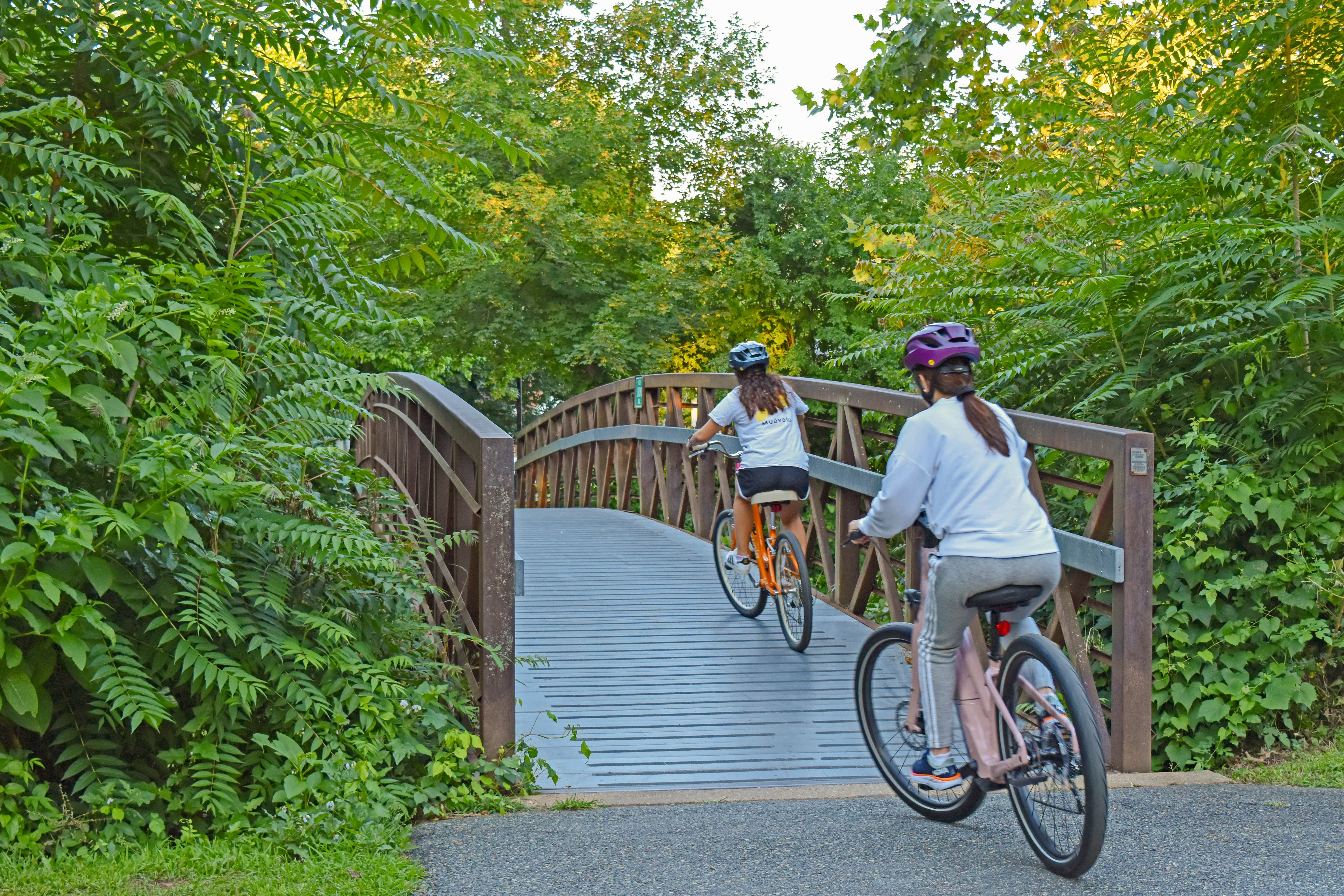 Two people ride their bikes over the Canal Path Bridge