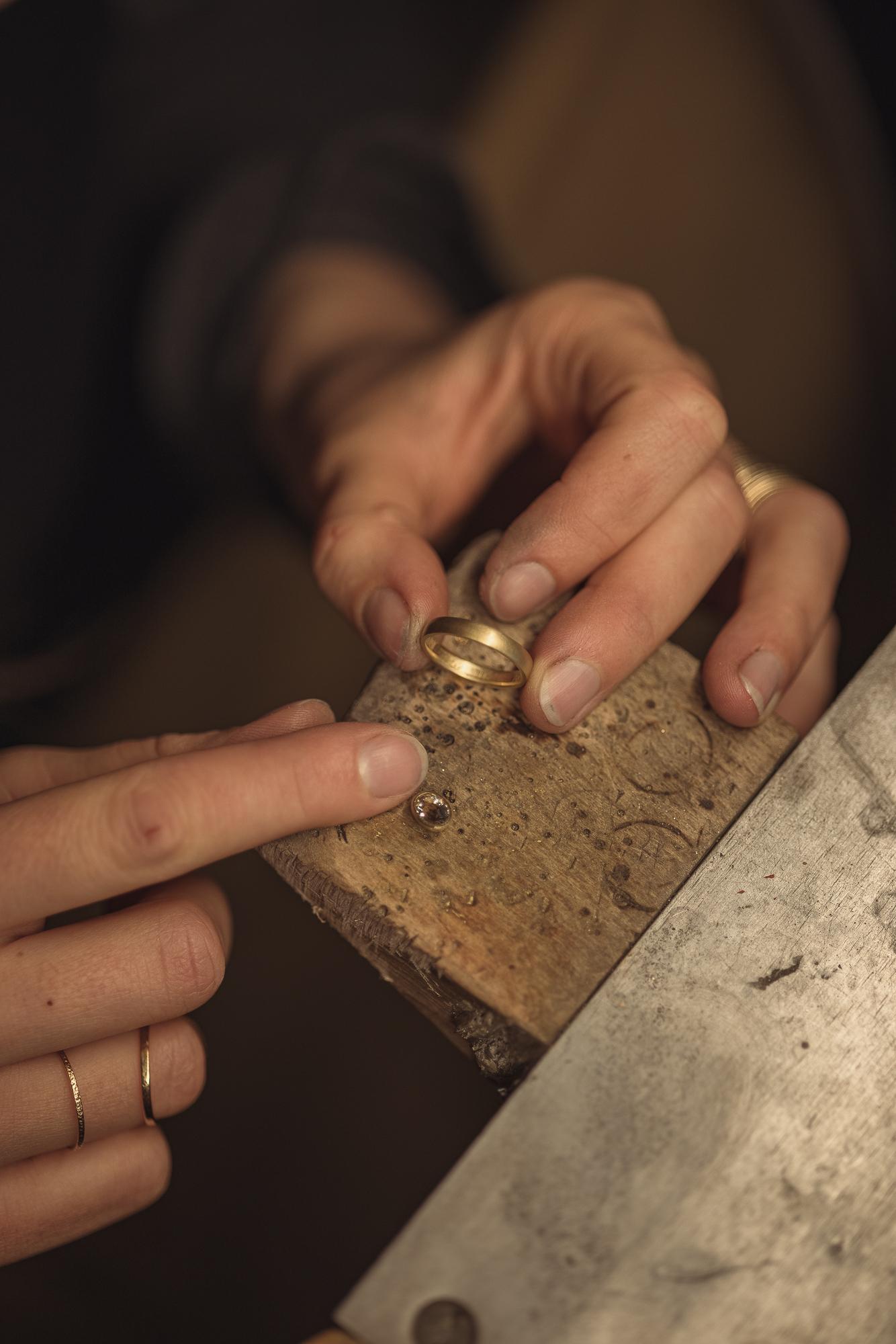 Foto von den Händen einer Goldschmiedin welche an einem Goldring arbeitet